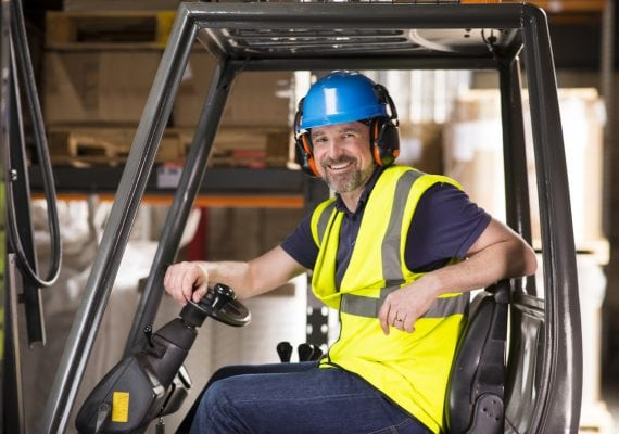 a mature man turns and smiles whilst seated at his forklift in a warehouse . he is wearing a hard hat and hi vis waistcoat and ear defenders .